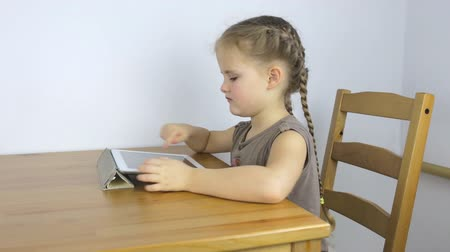 Little girl uses the tablet while sitting at the table Stockvideo