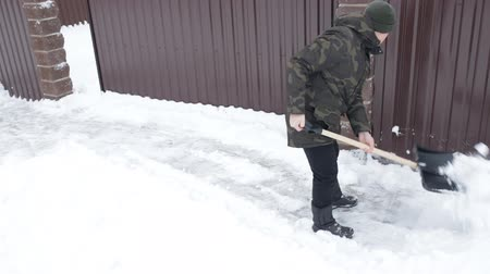 Man cleans the snow with a big shovel near the house