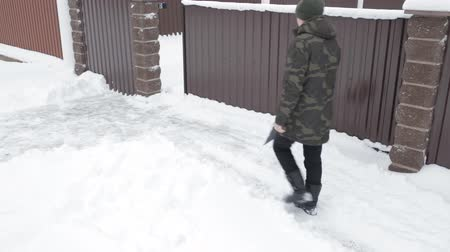 Man cleans the snow near the house with a big shovel