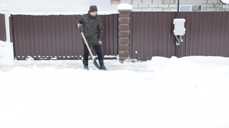 Man cleans the snow-covered road with a shovel Stock Footage