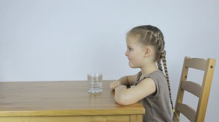 szomjúság : Girl drinks a tablet with her water