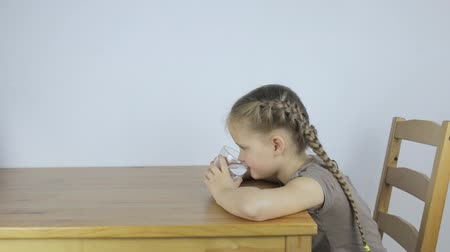 водянистый : Little girl drinks water from a glass while