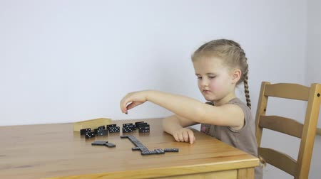 Little girl plays dominoes alone Stock Footage