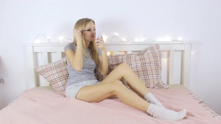 Girl does makeup sitting on the bed