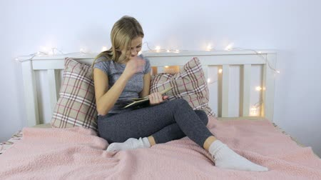 Girl in home clothes reading a book sitting on the bed