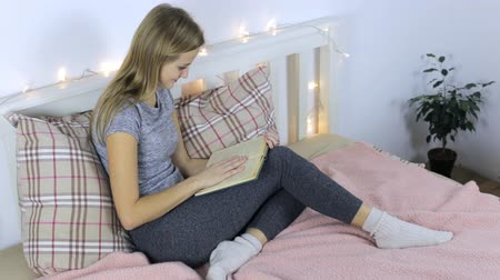Student reads a book while sitting bed Stockvideo