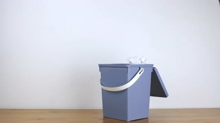 discard : Paper flies into an office bin that quickly fills