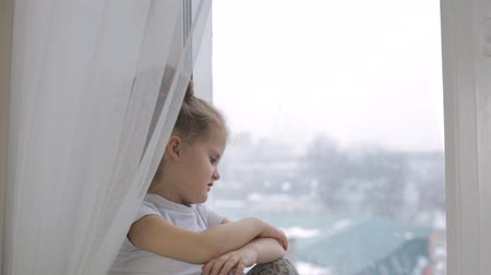 unalom : Sad little girl looks out the window, thinks about something and sentences it.