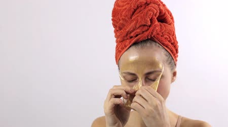 высокое разрешение : Close-up of a woman removing a golden mask from her face