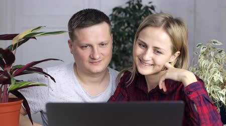 bakıyor : A young guy and a girl choose a new home, sitting behind a laptop monitor