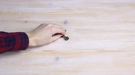 запомнить : Hand lifts a metal key from a wooden table