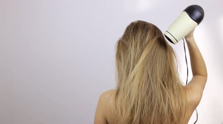 сушка : A girl is standing with her back and blow-drying her wet hair Стоковые видеозаписи