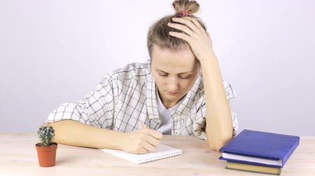 oturum : A tired student is engaged and falls asleep sitting at a table with textbooks Stok Video
