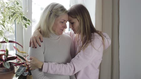 огорчен : Mother and daughter are embracing and sad