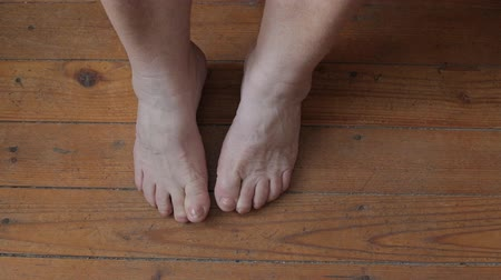 açı : Old female legs stand on a wooden floor