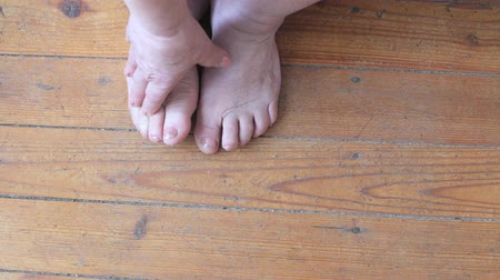 inflammation : Elderly woman massages feet standing on a wooden floor