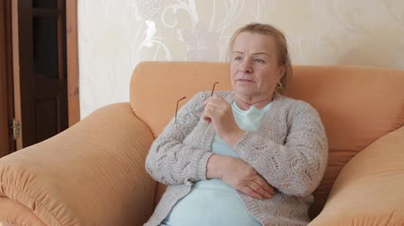 взял : Elderly woman took off her glasses and watches TV