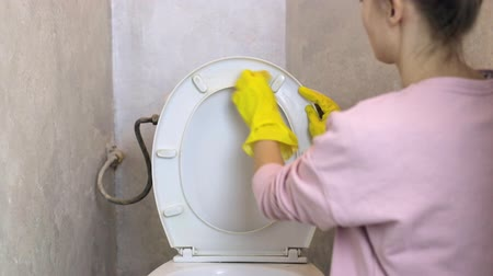 su tesisatı : Woman with yellow rubber glove cleans the toilet Stok Video