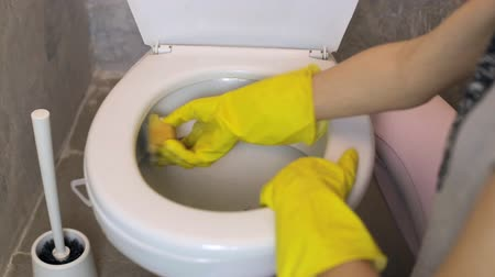 sanitize : Woman cleans white toilet with a sponge