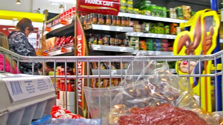 raflar : Grocery cart passing through the shop wth people passing. Stok Video