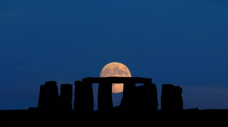 magical : Ancient Stonehenge during and full moon passing in the sky.