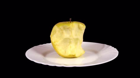 morder : Golden Delicious apple on a white place being eaten and turnning.