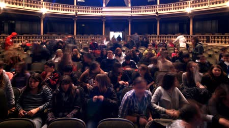 divadlo : People coming to their seats and leaving in the theatre.