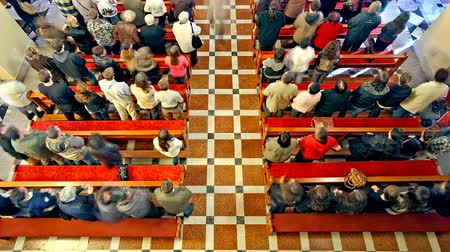sacramental : People standing up and sitting down in the pews during the mass.