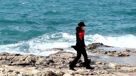 başörtüsü : Woman with red scarf walking by the sea. Stok Video