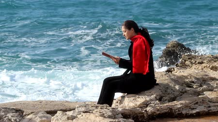 исцелять : Woman reading a book by the sea. Стоковые видеозаписи