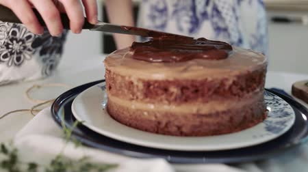 pekař : Baker decorated chocolate cake with chocolate topping, kitchen, the process of cooking cake