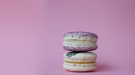 вкусности : Macaron. Desserts on a bright pink background. Female hand puts cakes pyramid