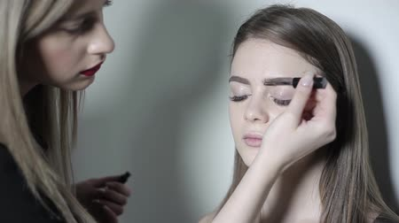 губная помада : Makeup artist doing makeup for eyebrows. Young girl doing professional makeup, eyebrow shaping