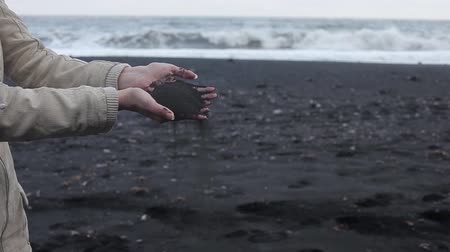 seu : Iceland, black sand. Female hands close up, to pour sand through fingers
