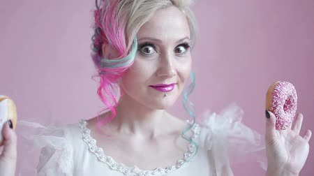 desery : Funny stylish woman with colored hair, play with doughnuts