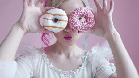 bécsi kifli : Funny stylish woman with colored hair, play with doughnuts