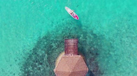 sucção : The girl on the SUP Board swims near the pier. The purest turquoise water. Paradise nature on a tropical island