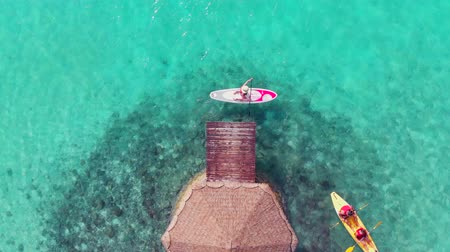 sup : The girl on the SUP Board swims near the pier. The purest turquoise water. Paradise nature on a tropical island