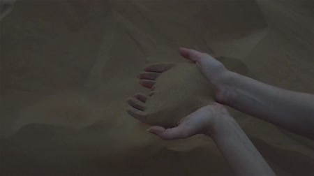 sandpit : Sand through fingers. Desert. The young woman scooped up the sand with her hands