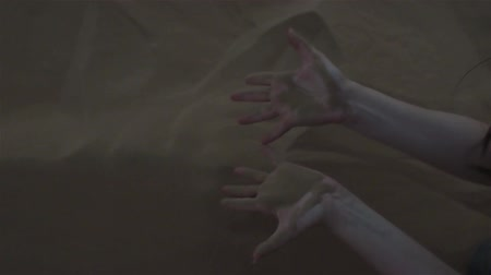 erozyon : Sand through fingers. Desert. The young woman scooped up the sand with her hands