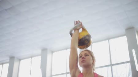 pulling up : young woman athlete performs a jerk kettlebell. Stock Footage