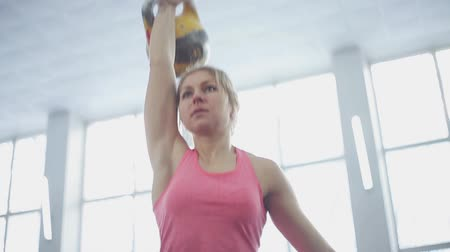 fegyelem : young woman athlete performs a jerk kettlebell. Stock mozgókép