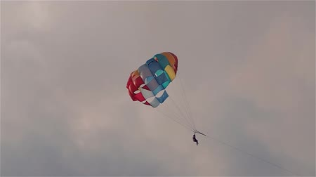 arrasto : Parasailing in evening. Bright parachute on a background of a sky.