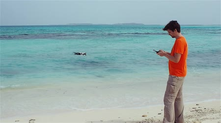 unmanned aircraft : guy launches a drone over the sea, photo and video shooting on quadrocopter.