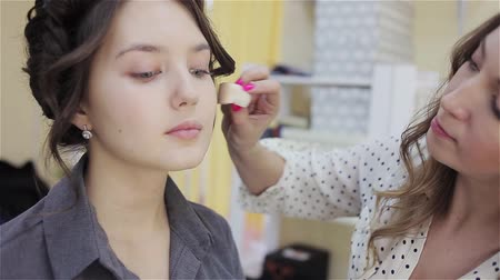 хозяин : Beautiful brunette girl uses the services of a professional makeup artist. Beauty shop. Make-up artist and her client