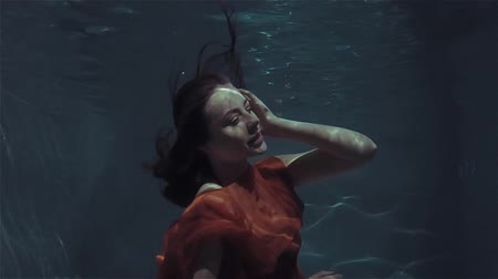 mermaid : Mystical underwater portrait of a beautiful young woman in a red dress.