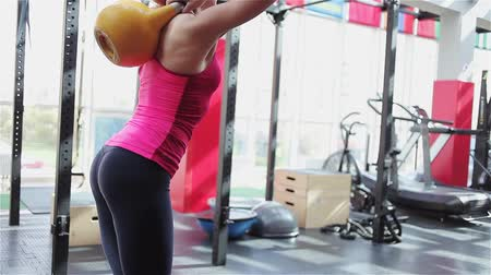 tilts : Kettlebell fitness, young female athlete doing strength exercises in the gym