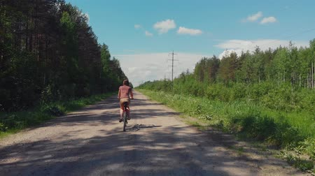 Girl on a Bicycle rides on a dirt road in the village. Cycling on the nature, forest. 影像素材
