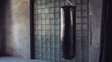 none : Dark grunge gym, punching bag swinging from the kick, nobody.