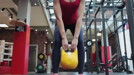 squat : Kettlebell fitness, young female athlete doing strength exercises in the gym